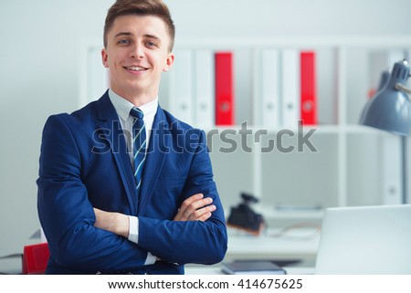Portrait of handsome confident young businessman standing arms crossed, smiling happy, looking at camera, photo with depth of field - stock photo
