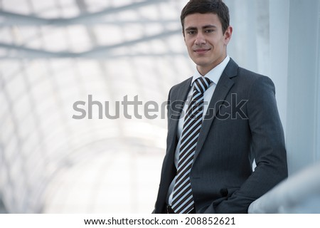 Portrait of handsome confident young businessman standing relaxed, smiling happy, looking at camera. - stock photo