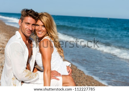 Portrait of handsome couple in white sitting on beach.