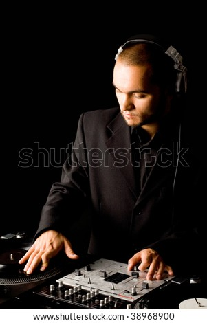 Portrait of handsome deejay at work spinning turntables