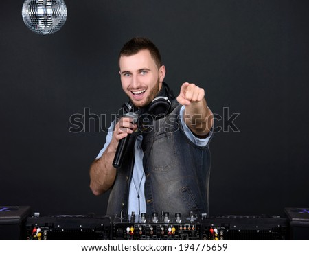 Portrait of handsome deejay playing club music - stock photo