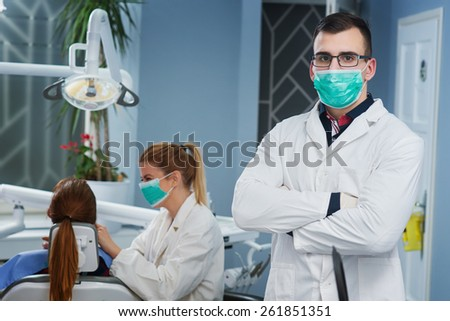 Portrait of handsome doctor at dentist office. Bright and natural lighting.  - stock photo