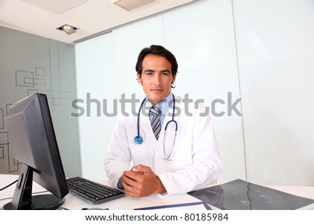 Portrait of handsome doctor sitting in office - stock photo