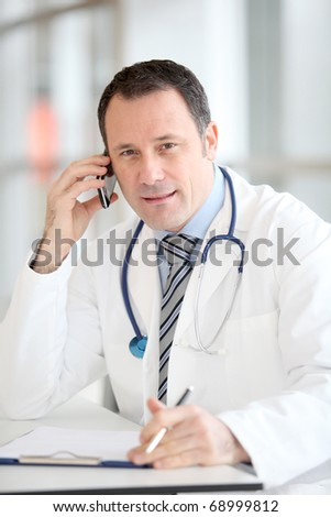 Portrait of handsome doctor talking on the phone