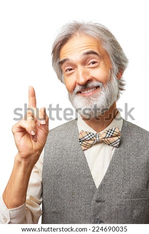 Portrait of handsome elderly man with gray beard and bowtie has an idea pointing finger up isolated on white background - stock photo