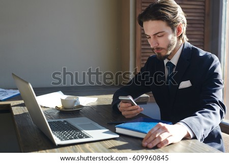 Portrait of handsome elegant businessman working with smartphone and laptop at wooden sunlit table