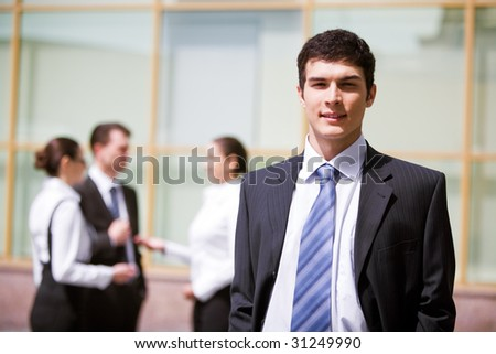 Portrait of handsome employer smiling at camera with consulting staff on background - stock photo