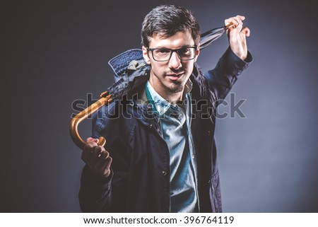 Portrait of handsome fashionable casual man holding  umbrella. Young guy posing in studio. Winter or autumn fashion vintage image on dark background.  Portrait of young handsome man   - stock photo