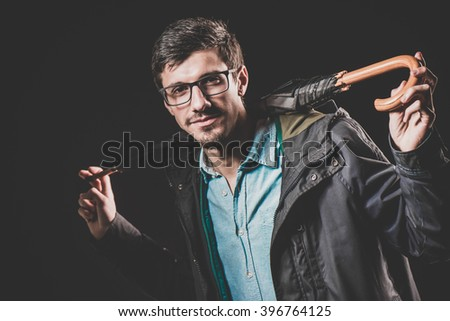Portrait of handsome fashionable casual man holding  umbrella. Young guy posing in studio. Winter or autumn fashion vintage image on dark background.  Portrait of young handsome man