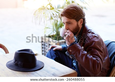 Portrait of handsome fashionable hipster man drinking tea or coffee while sitting on the terrace of beautiful coffee shop, flare sun light - stock photo