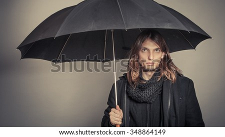 Portrait of handsome fashionable man wearing black coat and scarf holding umbrella. Young guy posing in studio. Winter or autumn fashion. Instagram filter. - stock photo
