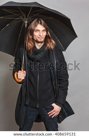 Portrait of handsome fashionable man wearing black coat and scarf holding umbrella. Young guy posing in studio. Winter or autumn fashion. - stock photo