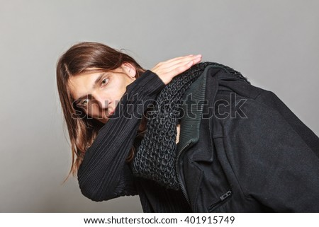 Portrait of handsome fashionable man wearing black sweater and scarf holding coat. Young guy posing in studio. Winter or autumn fashion. - stock photo