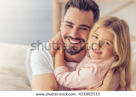 Portrait of handsome father and his cute daughter hugging, looking at camera and smiling