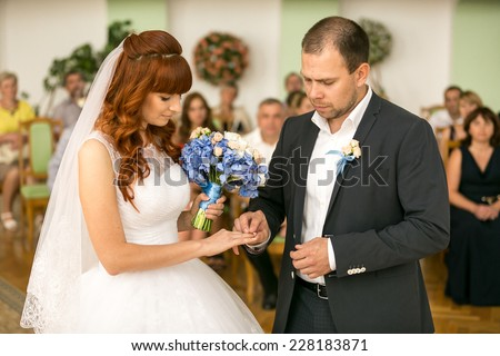 Portrait of handsome groom putting wedding ring on brides hand at registry office - stock photo
