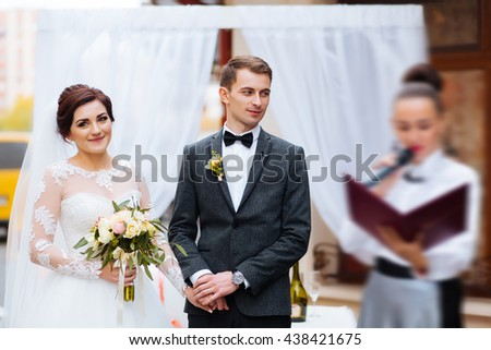 Portrait of handsome groom putting wedding ring on brides hand at registry office