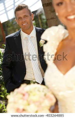 Portrait of handsome groom smiling happy on wedding-day. Outdoor photo.