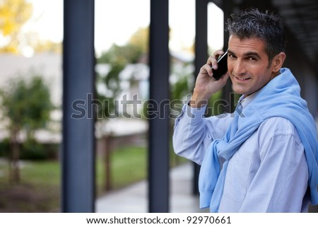 Portrait of handsome guy talking on cell phone - stock photo