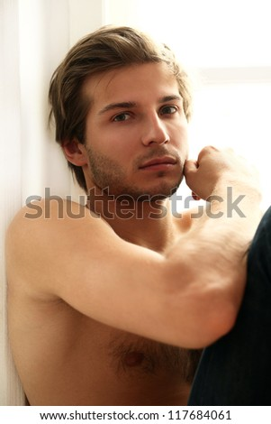 Portrait of handsome guy with naked torso sitting at the window