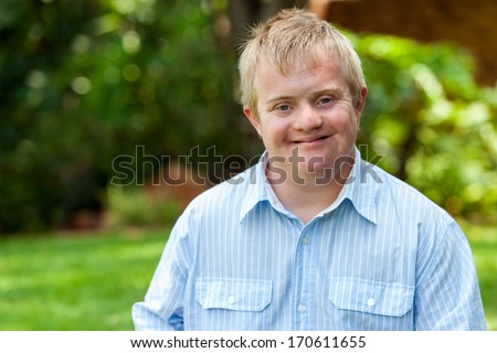 Portrait of handsome handicapped boy in blue shirt outdoors.