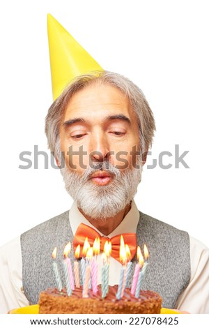Portrait of handsome happy caucasian aged man with a gray beard and orange bowtie in the yellow festive hood blowing candles on birthday cake isolated on white background - stock photo