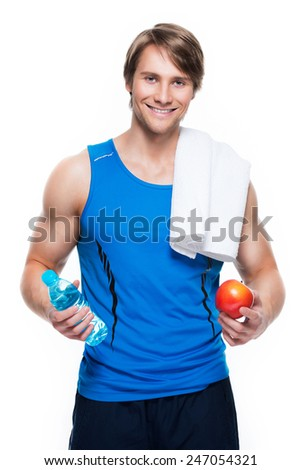 Portrait of handsome happy sportsman in blue shirt holds water and apple over white background. - stock photo
