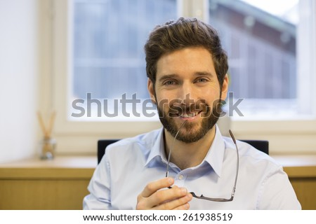 Portrait of handsome hipster style bearded man in office. Looking camera