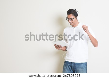 Portrait of handsome Indian guy using tablet pc and listening to music with headphones, standing on plain background with shadow, copy space at side. - stock photo
