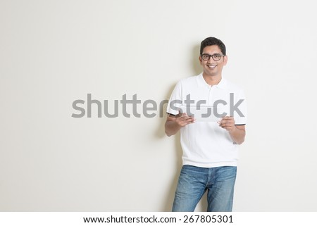 Portrait of handsome Indian guy using tablet pc, standing on plain background with shadow, copy space at side. - stock photo