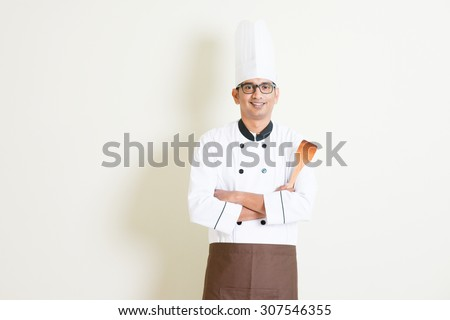 Portrait of handsome Indian male chef in uniform hand holding spatula and smiling, standing on plain background with shadow, copy space on side. - stock photo