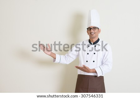 Portrait of handsome Indian male chef in uniform hands gesturing showing something and smiling, standing on plain background with shadow, copy space at side. - stock photo