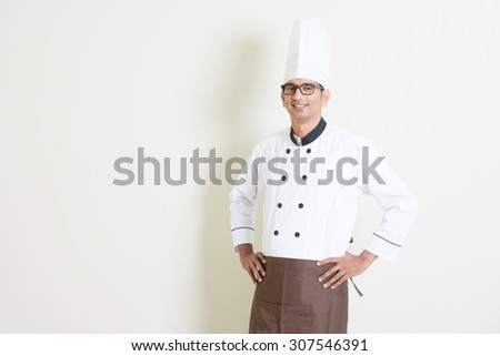 Portrait of handsome Indian male chef in uniform hands on waist and smiling, standing on plain background with shadow, copy space on side. - stock photo