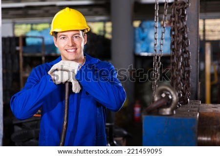 portrait of handsome industrial worker in workshop - stock photo