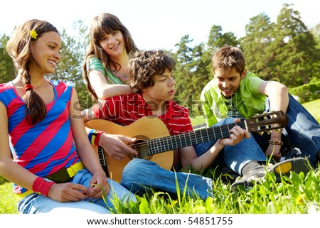 Portrait of handsome lad playing the guitar surrounded by his friends - stock photo