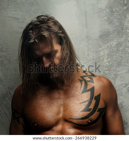 Portrait of handsome long-haired man with naked torso. Isolated on gray background. Tattoed male body.