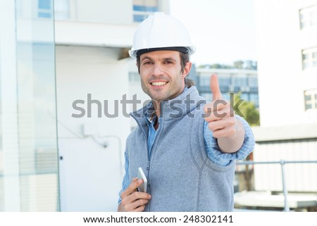 Portrait of handsome male architect gesturing thumbs up outdoors - stock photo