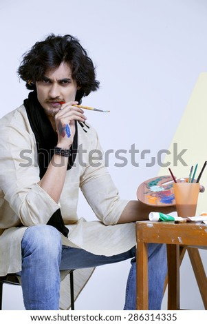 Portrait of handsome male artist with palette and paintbrush against colored background - stock photo