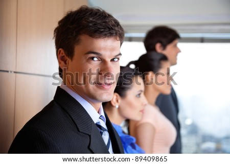 Portrait of handsome male executive smiling with colleagues standing besides him - stock photo