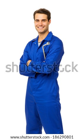 Portrait of handsome male mechanic in overalls holding wrench over white background. Vertical shot. - stock photo