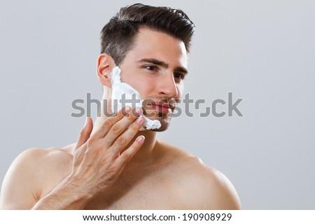 Portrait of handsome man applying shaving cream on his face,Preparation for shaving - stock photo