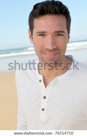 Portrait of handsome man at the beach - stock photo
