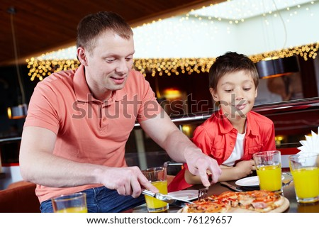 Portrait of handsome man cutting pizza with his son near by in pizzeria - stock photo