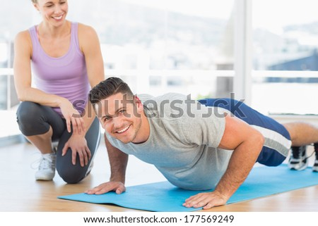 Portrait of handsome man doing push ups with female trainer in fitness studio - stock photo