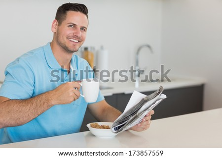 Portrait of handsome man having breakfast while holding newspaper at table in kitchen - stock photo