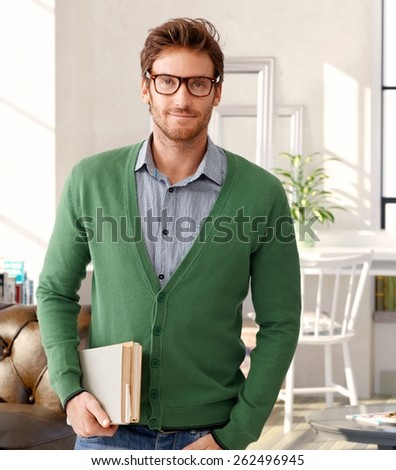 Portrait of handsome man holding books, wearing glasses. - stock photo