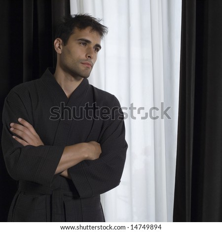 portrait of handsome man in a brown bathrobe in front of a window - stock photo