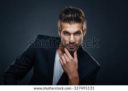 Portrait of handsome man in a studio on a dark background - stock photo