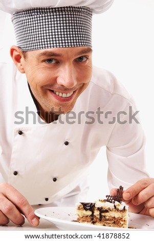 Portrait of handsome man in cook uniform looking at camera with tasty piece of cake near by - stock photo