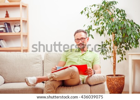 Portrait of handsome man in glasses looking at camera. Man sitting on sofa or couch and working with documents. Freelance or business concept.