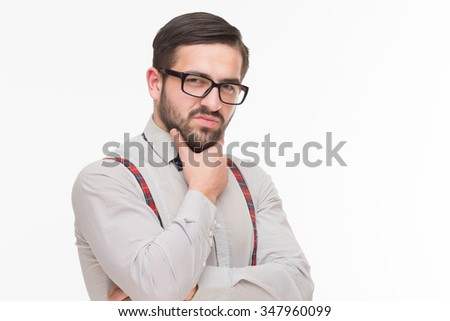 Portrait of handsome man in glasses posing for photographer in studio. Serious man in white shirt and braces looking at the camera. - stock photo